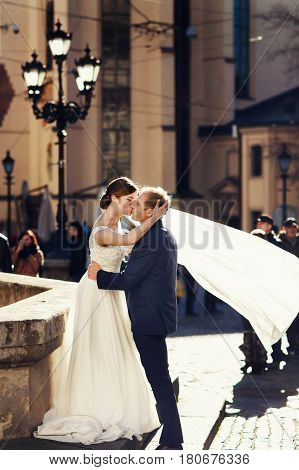 Wind Blows Bride's Veil Away While She Stands In Groom's Hugs