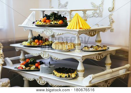Fruits lie on the trays on old-fashioned tired buffet