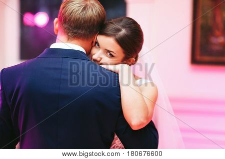Bride Looks From The Groom's Shoulder While Dancing With Him