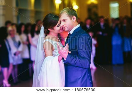 Bride Leans To A Groom Dancing With Him In A Hall Fool Of People