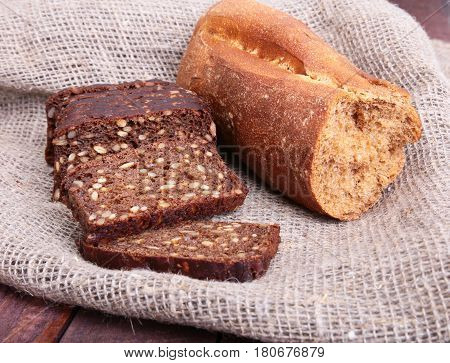 Assorted fresh breads, slice and knife isolated on old wood table