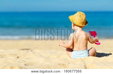 baby boy sit back with toys and sand on beach