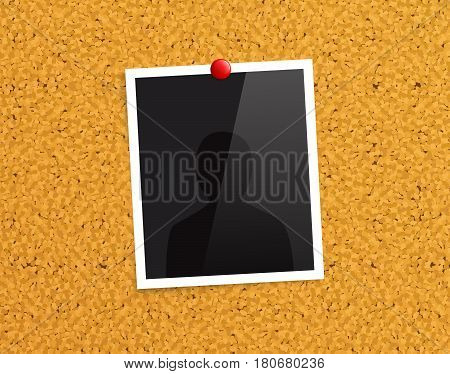 Empty photo frame pinned to a cork notice board with red push pin.