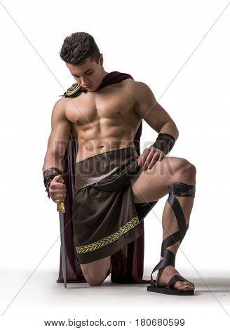 Young handsome muscular man posing in roman or spartan gladiator costume with shield and sword, isolated on white background in studio