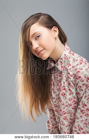 Portrait of pretty cute girl winking over grey background. Looking at camera. Positive human emotion facial expression body language, concept of funny girl