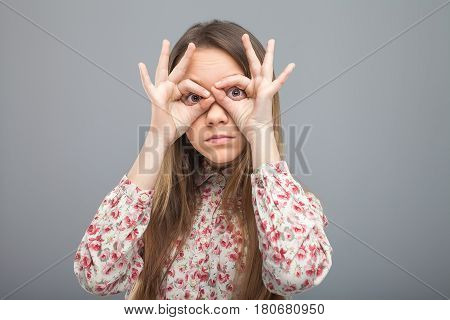 Funny lifestyle portrait of pretty woman in bright stylish party dress having fun and making a pair of glasses with her hands.