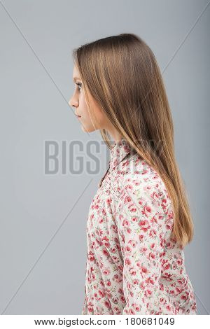 Young pretty blond model girl in blouse with a pattern of flowers. Long straight hair. Emotionless