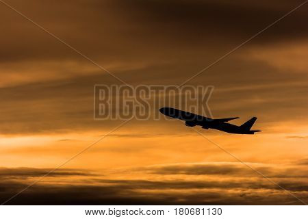 Silhouette airplane in the sunset sky, transportation and travel concept.