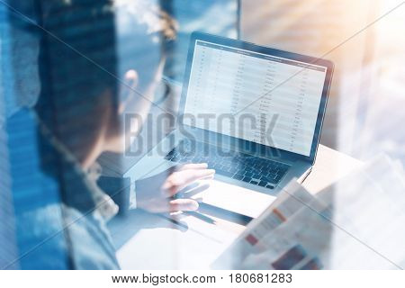 Closeup view of banking finance analyst in eyeglasses working at sunny office on laptop while sitting at wooden table.Businessman analyze stock report on notebook screen.Double exposure concept