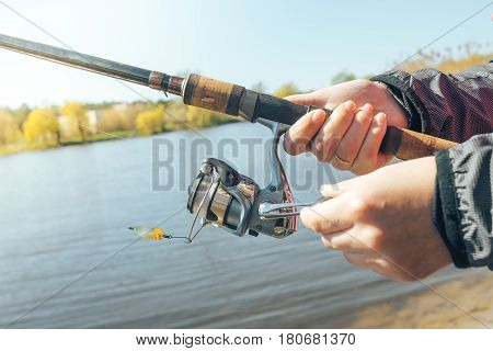 Girl's hand holding a fisherwoman spinning. The concept of fishing on a spinning