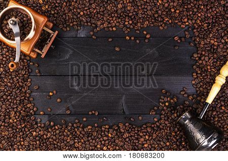 Coffee background, top view with copy space. Ground coffee, coffee mill, bowl of roasted coffee beans on dark wooden background
