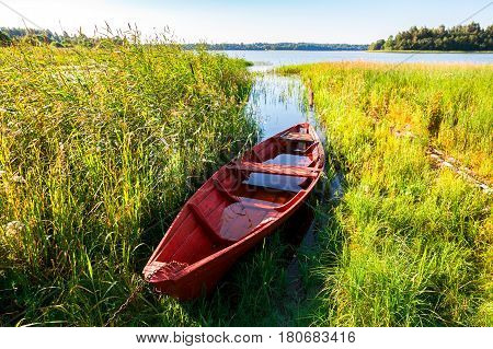 Old fishing wooden boat at the lake in summer sunny day