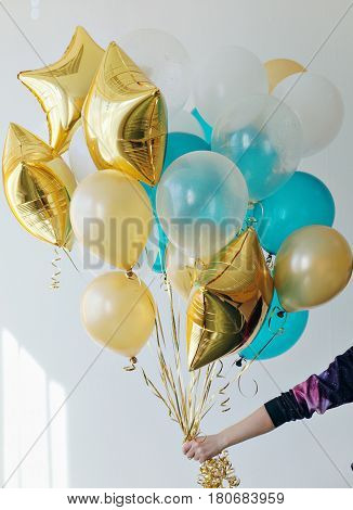 Hand of a person holding a bunch with common and star shaped balloons.