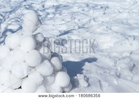 A slide made of several round white snowballs lying on the snow. A pyramid of three dozen snowballs.