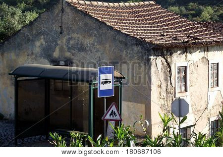 Deserted old house with modern bus stop outside