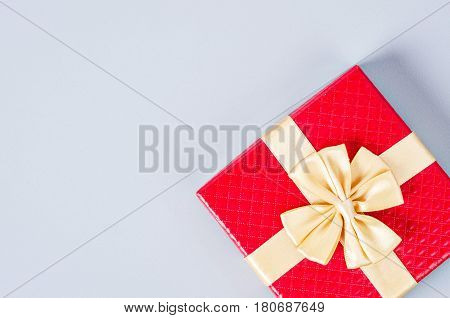 Red gift box with gold ribbon on gray background with copy space.