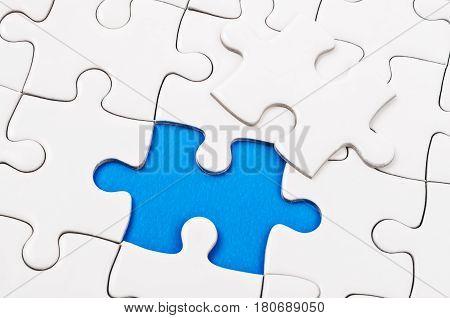 Plain white jigsaw puzzle on blue background.