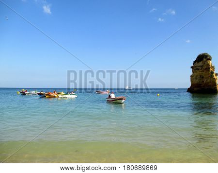 Portugal. Algarve. Lagos. Praia de Dona Ana. Boats and part of rock in the aqua of ocean on blue sky background. Horizontal view