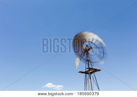 Close Up Wide Angle Image Of A Windmill / Windpomp With Spinning Blades, Pumping Water In The Tankwa