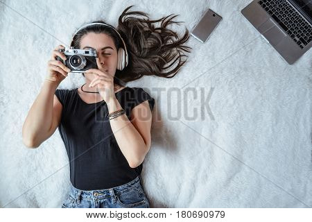 woman taking picture in bed while listening music