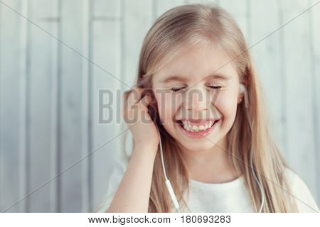 A young girl with earphones is shutting her eyes and smiling from ear to ear at the same moment