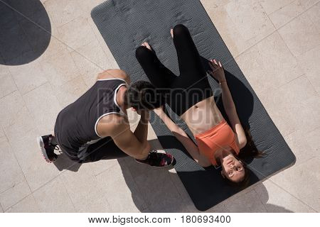 young handsome woman with personal trainer doing morning yoga exercises in front of her luxury home villa top view
