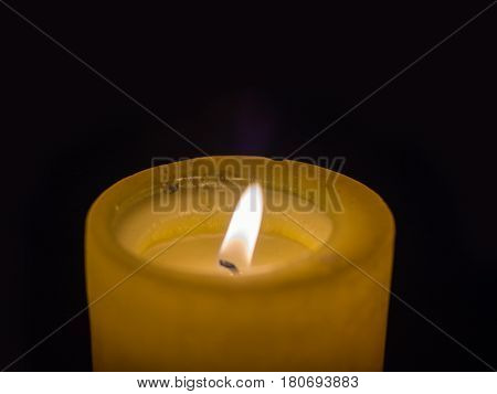Large, burning, wax candle on a dark background with flaming, burning fuse, close-up photo with soft, blurred focus.