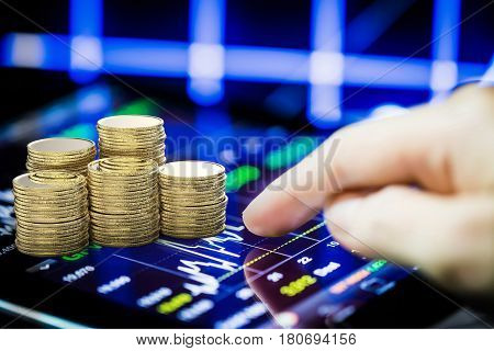 stock market watching with digital tablet and stack of gold coins