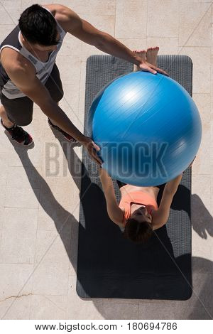 young beautiful woman and personal trainer doing exercise with pilates ball in front of her luxury home