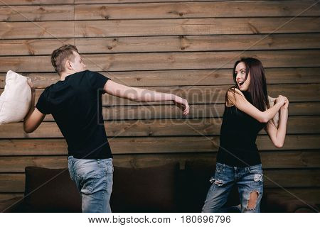 couple having pillow fight at home. They wear in black shirt and jeans and stand on bendend knees on the bed. Everyone is holding a pillow