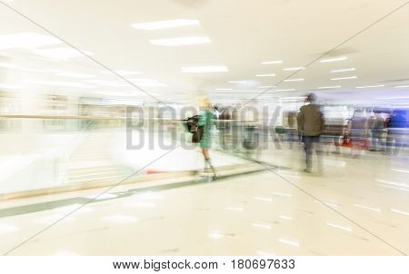 Crowd rushing inside a modern wide bright mall hall with boutiques glass display windows people incognito in motion blur horizontal view