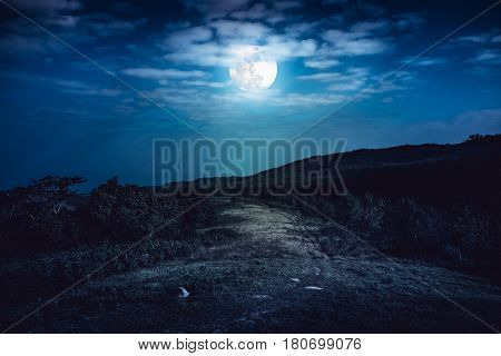 Landscape in nature of beautiful full moon behind cloud and roadway through a forest. Mountain road passing outdoors at nighttime. Dark tone. The moon were NOT furnished by NASA.