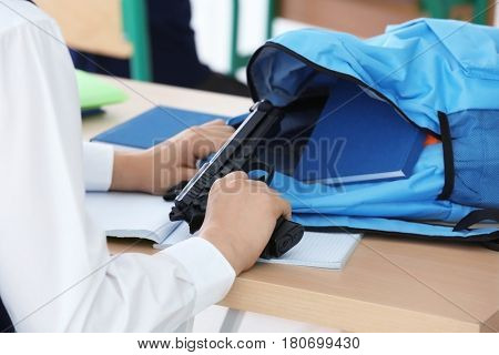 Closeup of schoolboy sitting at desk in classroom and taking gun out of backpack