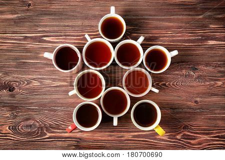 Delicious tea in cups forming star on wooden background