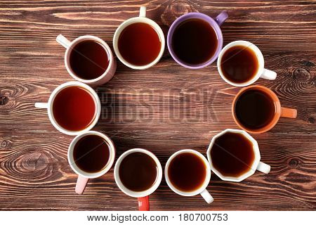 Delicious tea in cups forming circle on wooden background