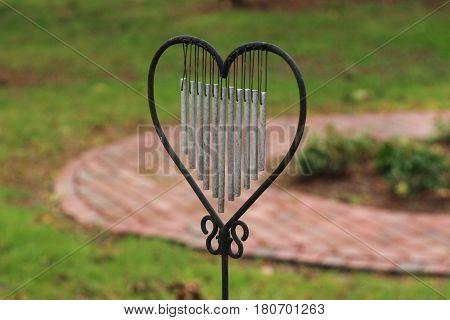 Wrought iron heart shape chimes in a garden.