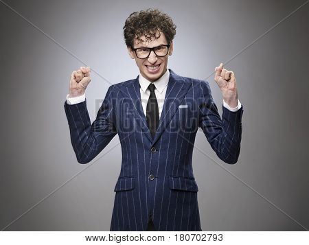 Super excited funny evil genius businessman. Professional actor facial expression. Toothy smiling clenching fists. poster