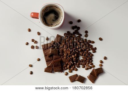 Cup Of Hot Coffee, Beans Coffee And Chocolate On White Table