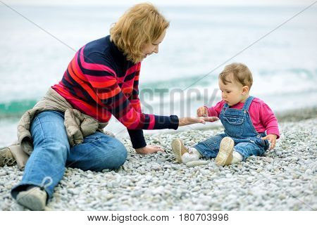 Baby girl and her mother playing with pebbles on the beach