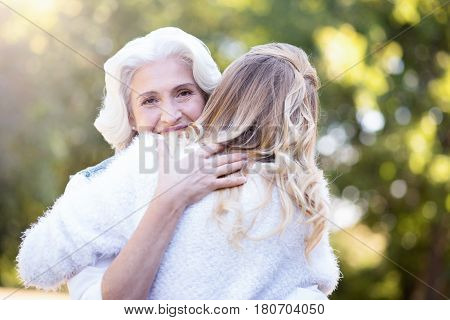 Sharing my love with you. Pleased loving retired woman walking in the park while expressing love and hugging mature daughter