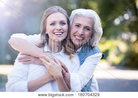 Enjoying hugs. Cheerful attractive young woman walking in the park while expressing delight and hugging aging parent