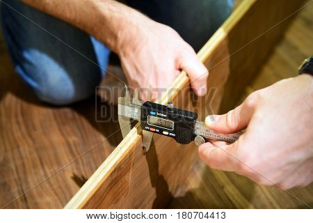 Carpenter measures the thickness of the laminate board with electric calipers during the flooring.