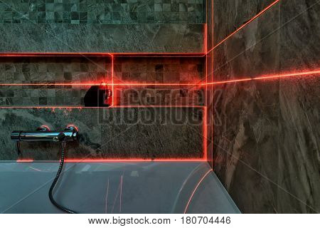 A red laser measurement during bathroom renovation