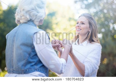 Mitting of generations. Young beautiful cute woman walking outdoors while expressing love and holding hands with grandmother