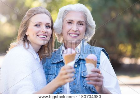Enjoying warm weather. Delighted joyful young woman enjoying the weather outdoors while expressing happiness and eating ice cream with old mother
