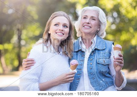 Happy mothers day. Smiling loving aged woman enjoying the sunny weather outdoors while tasting dessert and hugging mature daughter