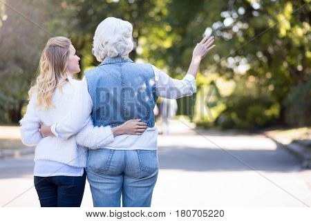 Enjoying our day. Inspired greyish aged woman enjoying the sunny weather outdoors while expressing joy and hugging mature daughter