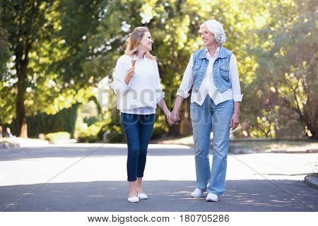 Enjoying active weekend . Delightful greyish old mother enjoying the sunny weather outdoors while expressing joy and holding hands with mature daughter