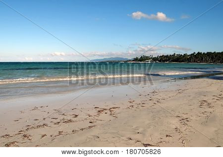 Ocean and tropical sandy beach near blue sky. Background of summer holiday and vacation.Dominican Republic.
