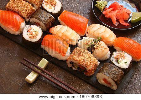 sushi and sushi rolls sushi nigiri on stone plate on dark background